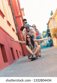 Group of friends having good time at the city street with skateboard.