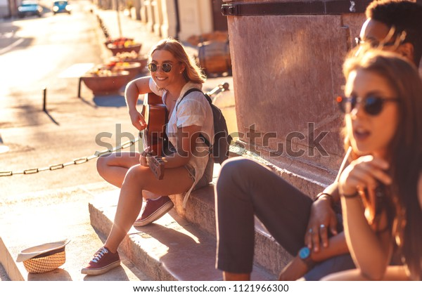 Group of friends having good time at the city street. Girl playing guitar.