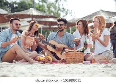 Group of friends having great time together on the beach,eating pizza,play guitar and enjoy.