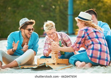 A group of friends having great time together on the beach and palying game.
