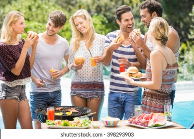 Group of friends having hamburgers and juice at outdoors barbecue party