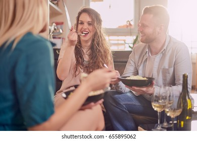 Group of friends having meal in living room while sitting on sofa