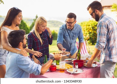 Group of friends having an outdoor barbecue lunch, eating grilled meat, drinking beer and having fun.