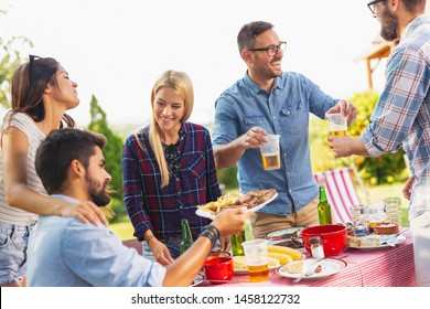 Group of friends having an outdoor barbecue lunch, eating grilled meat, drinking beer and having fun