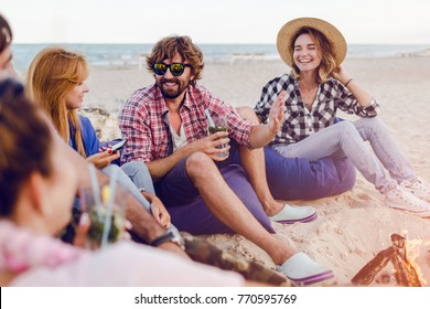 Group of friends having party around bonfire on the beach at sunset.  Hipster man with beard tells jokes. Warm colors. Holiday time.Sunset.
