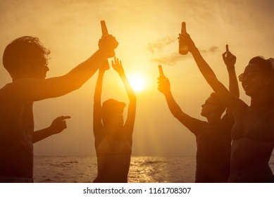 Group of friends having party celebrating and drinking at the beach in summer twilight sunset