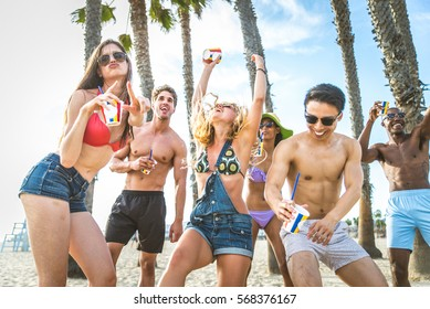 Group of friends having party on the beach, dancing and drinking cocktails