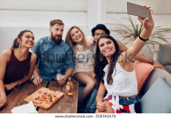 Gruppe von Freunden, die auf dem Dach eine Party machen, um sich an diesen perfekten Moment zu erinnern. Fröhliche und fröhliche junge Menschen, die sich selbst porträtieren.