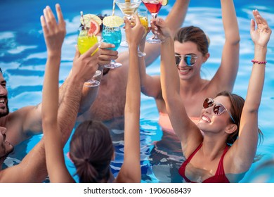 Group of friends having party in pool, drinking cocktails and enjoying together.
