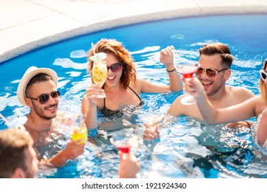 Group of friends having party in pool, drinking cocktail and enjoying together.