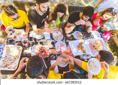 Group of friends having picnic at park. Large multiracial group of people sitting at a table and eating together on a summer day. Friendship, vacations and lifestyle concetps