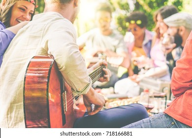Group of friends having a picnic in a park outdoor - Happy young mates enjoying pic-nic playing guitar, singing and drinking wine eating food - Recreation concept - Focus on man arm's with guitar