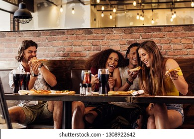 Group of friends having pizza at cafe. Cheerful young people eating pizza and enjoying at a fast food restaurant.