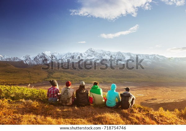 Group of friends having rest on the top of mountain on backdrop of glacier. Travel concept with space for text