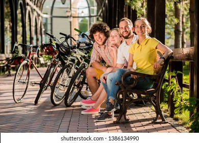 Group of friends having rest in park. Beautiful students in casual outfit resting with bicycles outdoors. Great day for cycling.