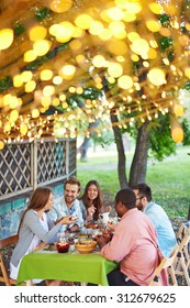 Group of friends having traditional Thanksgiving dinner outdoors