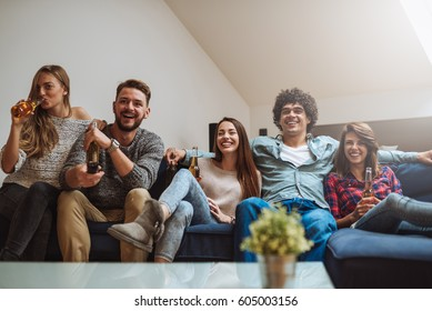 Group of friends having a wonderful time watching television at home.