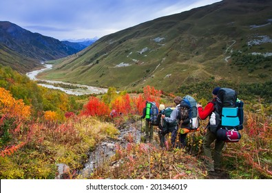 group of friends in hiking in high mountains.  snow-capped peaks, glaciers and  Fantastic sky background with blue clouds. Beautiful world