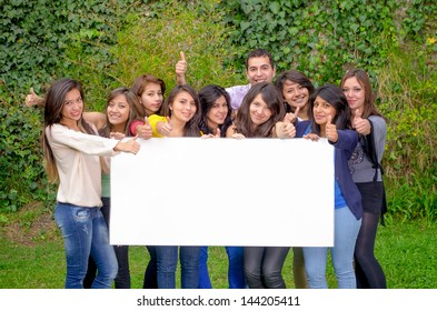 Group of friends holding blank sign outside