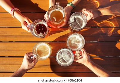 Group of friends holding glass mugs of beer on wooden background