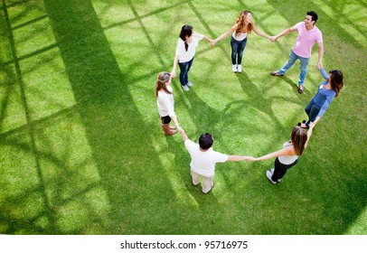 Group of friends holding hands in a circle - outdoors