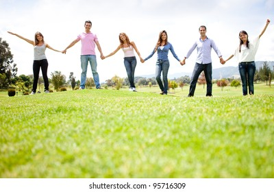 Group of friends holding hands outdoors having fun