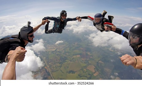 A group of friends holding hands teamwork in skydiving, soft focus on the clouds