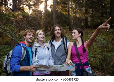 Group of friends holding a map and looking forward while hiking in the forest