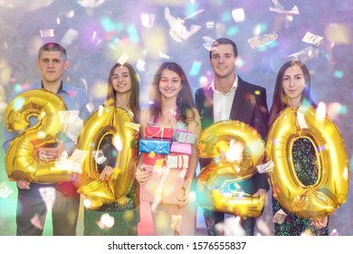 Group of friends holding present boxes and golden air balloons 2020 at new year party