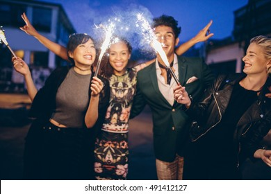 Group of friends holding sparklers out on street at night. Young men and women having night party with sparklers.