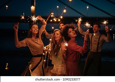 Group of friends holding sprinklers on a boat cruise