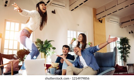 Group of friends at home party.  Dancing on the table and playing funny games together