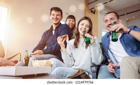 Group of friends at home party. Drinking beer, eating pop corn and pizza and watching tv series together. Multi ethnic people