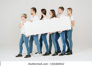 Group of friends in jeans holding a long blank white banner sign as they stand looking to the left of the frame over a white studio background