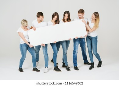 Group of friends in jeans and white t-shirts holding a blank white banner in front of them as they all look down at the copy space over a white studio background