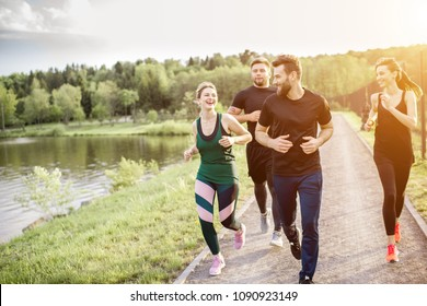 Group of friends jogging during the morning exercise in the park near the lake