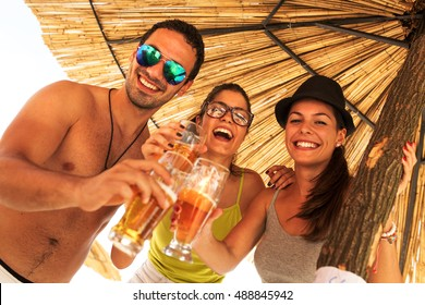 Group of friends joying in beer and music at the beach party.Summer fun.