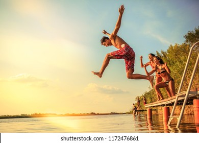 Group of friends jumping into the lake from wooden pier.Having fun on summer day.Sunset.