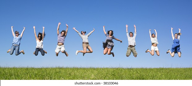 Group of friends Jumping in meadow under blue sky
