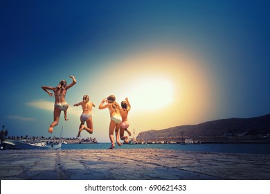 Group of friends jumping to the sea from the pier, happy beach holidays, Crete, Greece