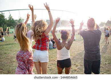 Group of friends jumping at summer music festival