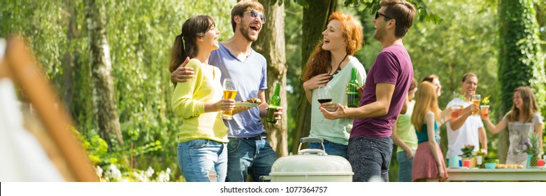Group of friends laughing at a barbeque party in a park