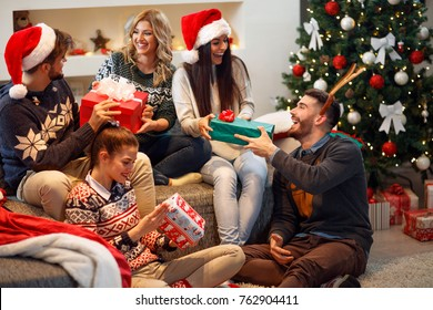 Group of friends laughing and sharing Christmas gifts