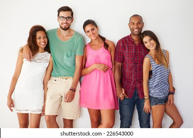 Group Of Friends Leaning Against White Wall