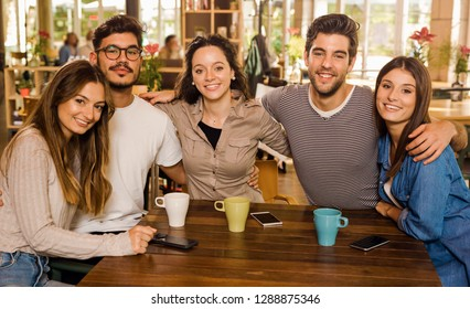 A group of friends looking to the camera and drinking coffee at the cafe