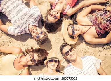 group of friends lying on the beach in a sunny day. concept about mixed race friends and vacations