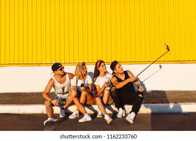 A group of friends makes a selfie sitting on the pavement, the company of young people taking pictures with a selfie stick, cheerful company, Sunny day