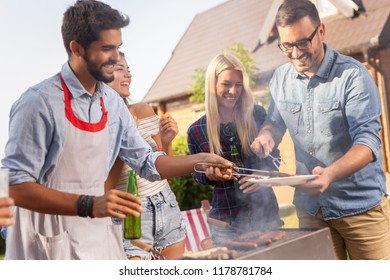 Group of friends making barbecue in the backyard, drinking beer and having fun on a sunny summer day. Focus on the girls