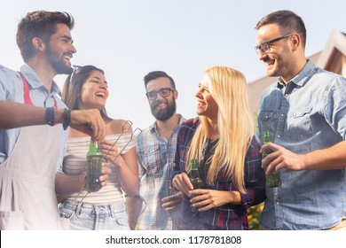 Group of friends making barbecue in the backyard, drinking beer and having fun on a sunny summer day. Focus on the girl on the right