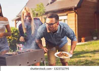 Group of friends making barbecue in the backyard and having fun on a sunny summer day